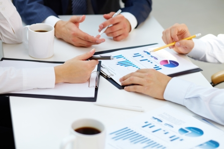 financial analysis: Close-up of business group analyzing financial papers for the certain period Stock Photo