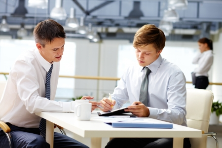 Senior businessman helping his younger colleague with financial analysis photo