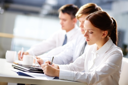 Group of business people taking notes at training photo