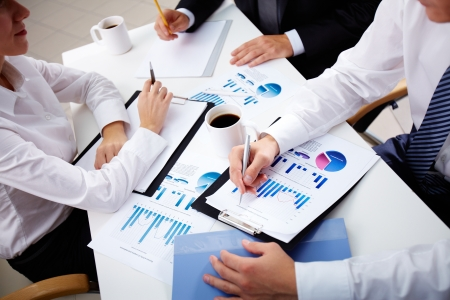revisando documentos: Equipo de negocios de tres análisis de datos estadísticos