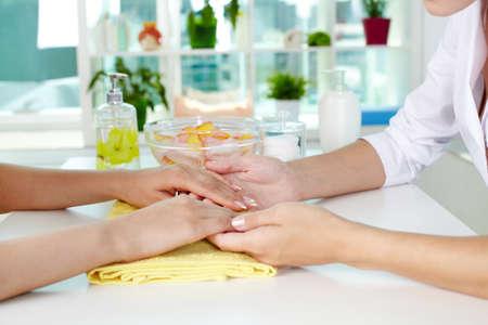 workplace wellness: Professional manicurist examining female hands