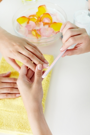 soaking: Hand care industry worker filing female nails