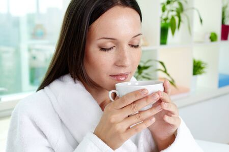 drinking tea: Beautiful brunette drinking herbal tea after spa procedures Stock Photo
