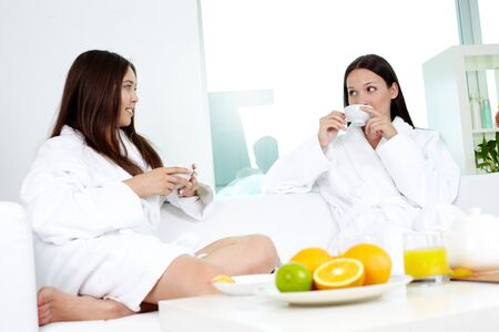 Attractive girls in bathrobes relaxing in spa drinking tea photo
