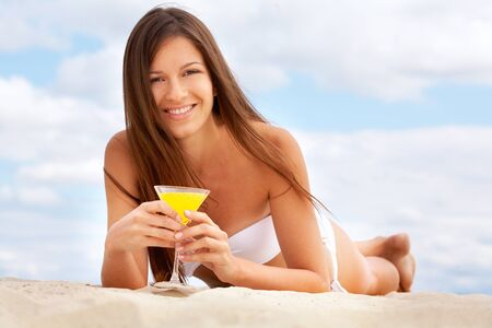 Tanning girl drinking fresh orange juice lying on the beach photo