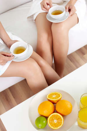 vertical wellness: Females enjoying their day in the spa with tea and fresh fruit Stock Photo