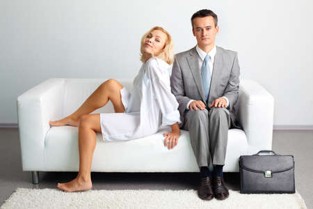 Embarrassed businessman sitting too close to a sensual woman in loose clothes photo