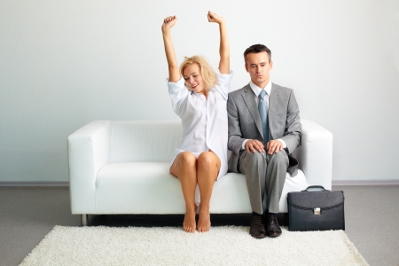 tensed: Sensual young lady in male shirt stretching herself sitting next to a tensed businessman after a night together