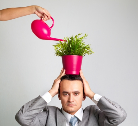 Serious businessman growing plant on his head photo