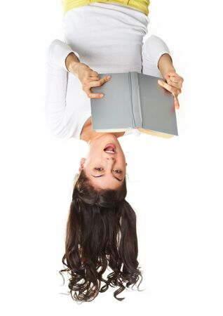lovely girl: Surprised teen reading book in an unusual position, isolated on white