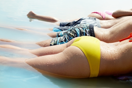 Close-up shot of male and female bodies in summer swimwear photo
