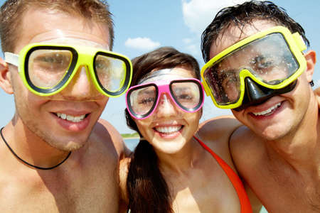 Portrait of three cheerful friends wearing scuba masks and smiling at camera photo