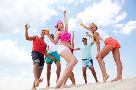 Dynamic friends having fun on the beach photo