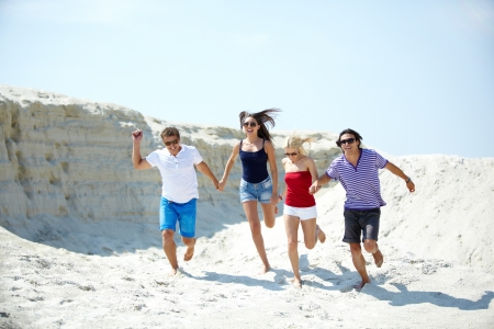 hand movement: Ecstatic young people running on the sand holding hands