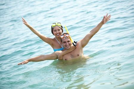 Friends wearing scuba masks having fun in summer water photo