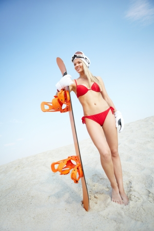 bikini slender: Vertical portrait of a lovely girl standing on sand with snowboard in her hands Stock Photo