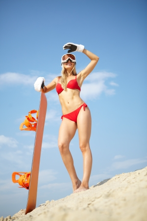 Sexy girl posing with snowboard on the beach waiting for winter season Stock Photo