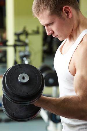 Imagen de la formación del hombre deportivo en el gimnasio con pesas Foto de archivo - 14644999