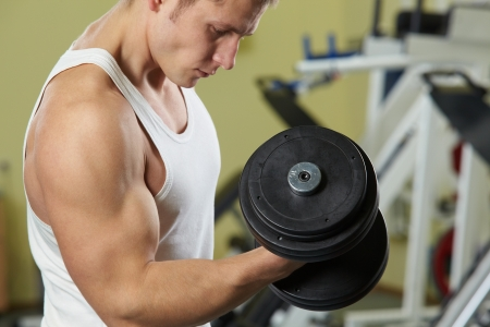 weightlifter: Image of sporty man training in gym with barbell