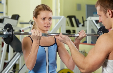 Portrait of sporty woman doing exercise with dumbbell and her trainer supporting  photo
