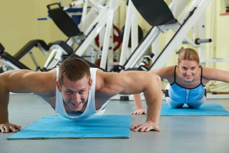 Portrait of sporty couple doing physical exercise and smiling at camera  photo