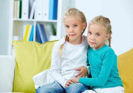 bambine gemelle: Ritratto di due gemelle seduta sul divano Archivio Fotografico