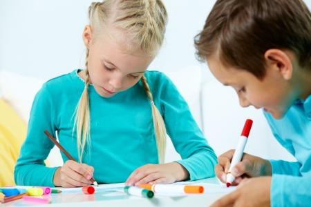 niños dibujando: Retrato de niña bonita y el dibujo niño con lápices de colores Foto de archivo