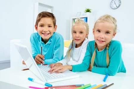 Smart schoolchildren working with laptop at home photo