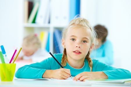 junior education: Portrait of lovely girl drawing with classmates on background