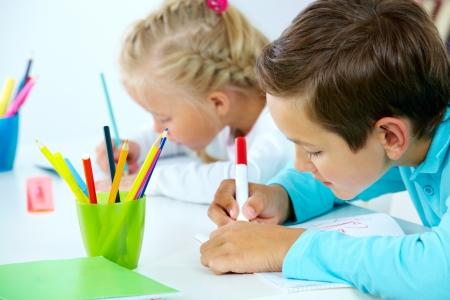 niños dibujando: Retrato de niño lindo dibujo con lápices de colores y su compañero de clase en el fondo Foto de archivo