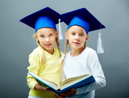 niñas gemelas: Retrato de dos niñas hermosas en sombreros con borlas celebración de libro abierto