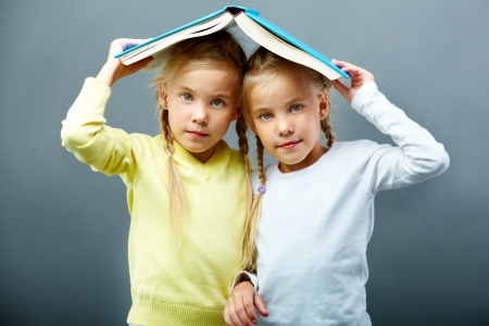 Portrait of lovely twin girls holding open book over heads photo