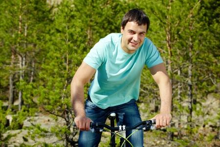 Portrait of a handsome man riding a bike photo