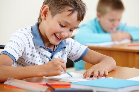 niños escribiendo: Retrato de muchacho de dibujo inteligente en la lección con su compañera en el fondo