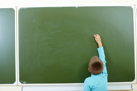 Photo of smart pupil going to write something on blackboard photo