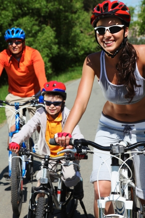 Portrait of happy woman in front of her family riding on bicycles photo
