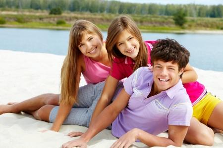 Portrait of three teenage friends on sandy beach photo