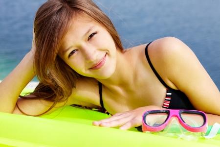 Portrait of teenage girl in bikini lying on mattress and looking at camera