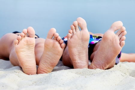 sandy feet: Soles of teenagers sunbathing on sandy beach