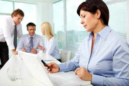 telephony: Mature businesswoman at workplace dialing phone number in working environment