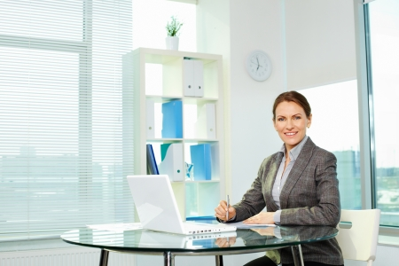 Cheerful business lady smiling at camera while sitting at her workplace photo