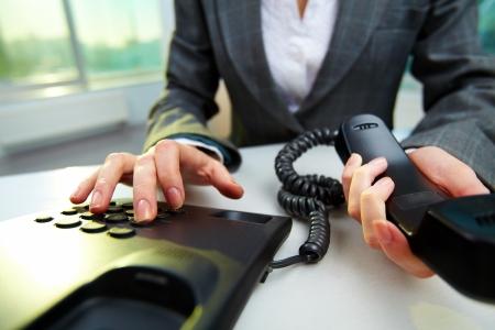 dialing: Mujer celebraci�n mano del tel�fono receptor y el n�mero de marcaci�n