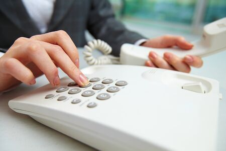 dialing: Female hand holding phone receiver and dialing number Stock Photo