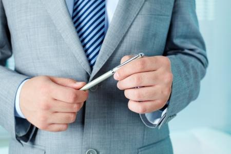 business attire teacher: Smart businessman holding pen