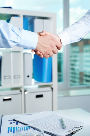 Photo of handshake of business partners after striking deal with signed documents on table photo