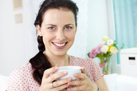 charmingly: Young girl with cup smiling charmingly at camera  Stock Photo