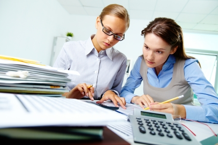 Portrait of two businesswomen working with papers in office Stock Photo - 14726879