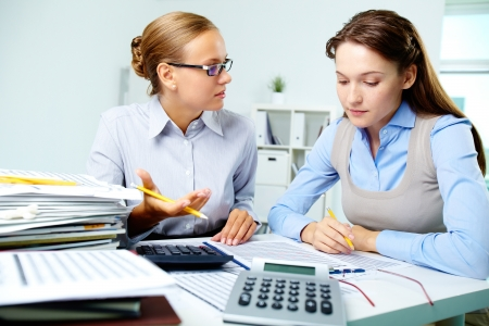 Portrait of young businesswomen interacting while working with papers in office photo