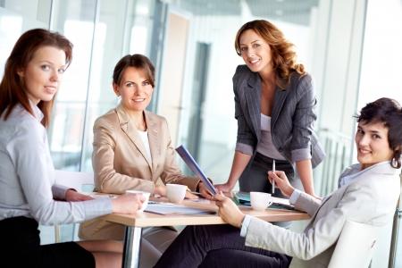 mujeres sentadas: Imagen de cuatro mujeres de negocios exitosas mirando a la c�mara a atender Foto de archivo