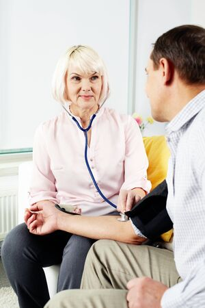 Portrait of mature woman measuring blood pressure of her husband at home Stock Photo - 14726931